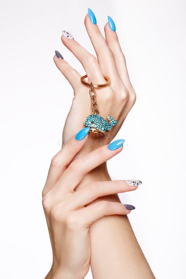 Manicura azul del verano hermoso con los cristales en la mano femenina Primer fotos de archivo libres de regalías