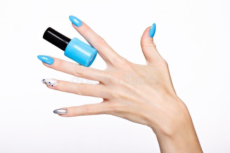 Manicura azul del verano hermoso en la mano femenina con el esmalte de uñas Primer foto de archivo libre de regalías