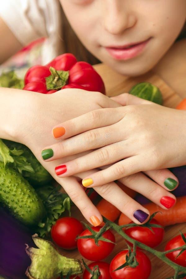 Manicura del ` s de los niños con el diseño colorido del esmalte de uñas para sus clavos fotos de archivo
