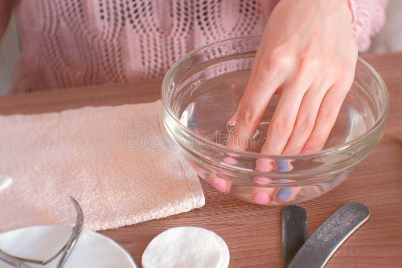 Manicura en casa Mujer que sumerge su mano en un cuenco de agua Dé el primer, herramientas de la manicura en la tabla imagenes de archivo