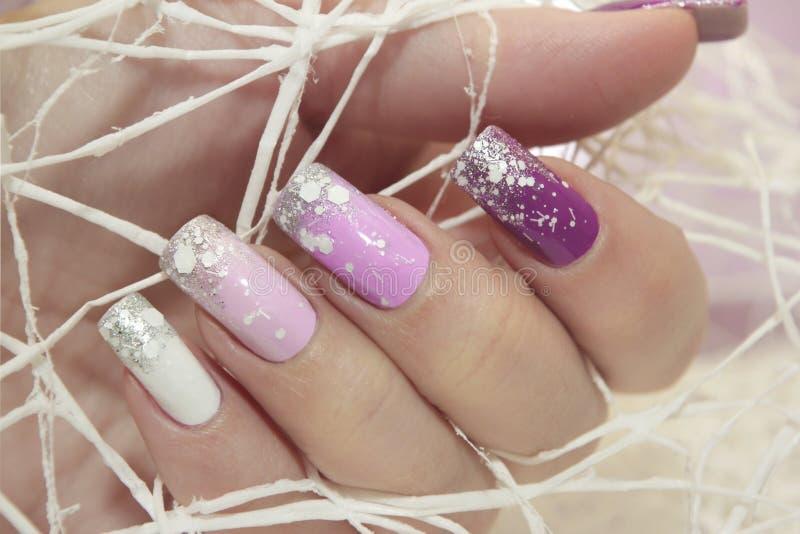 Manicura en colores pastel de la lila multicolora del invierno fotos de archivo libres de regalías