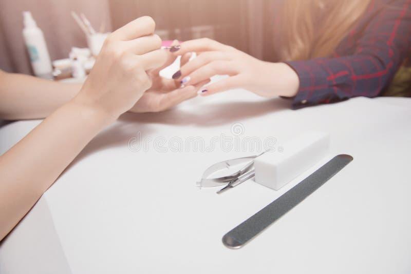 Manicura en el salón de belleza Aplicación de la capa del gel a la muchacha con el pelo largo Primer, iluminación caliente Foco e imagen de archivo libre de regalías