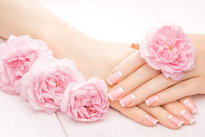 Manicura francesa con las flores color de rosa Spa fotos de archivo libres de regalías