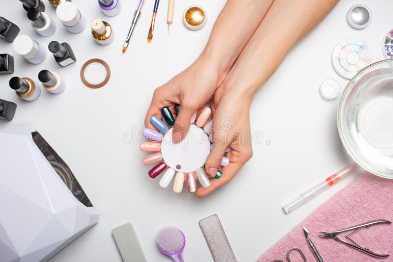 Manicura - la muchacha misma hace, mirando los clavos con la ayuda de una herramienta en un fondo blanco Concepto de salones de b fotos de archivo