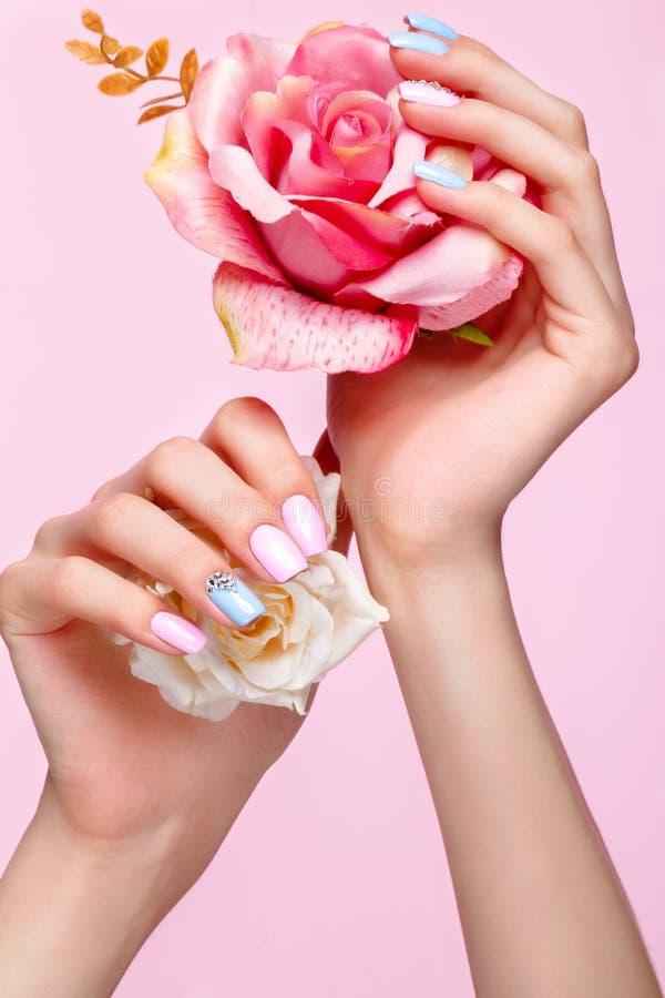 Manicura rosada y azul hermosa con los cristales en la mano femenina Primer fotografía de archivo
