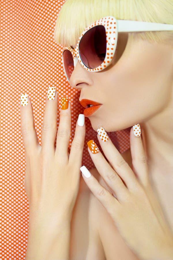 Manicura y maquillaje anaranjados soleados imagenes de archivo