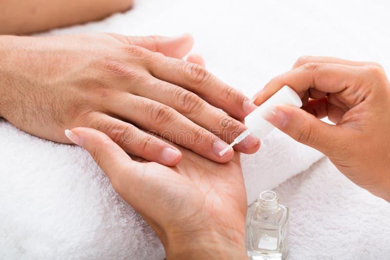Manicure Applying Moisturizing Oil op Persoons` s Hand stock afbeeldingen