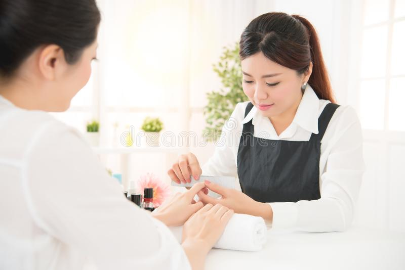 Manicure in beauty salon nail filing close up stock image