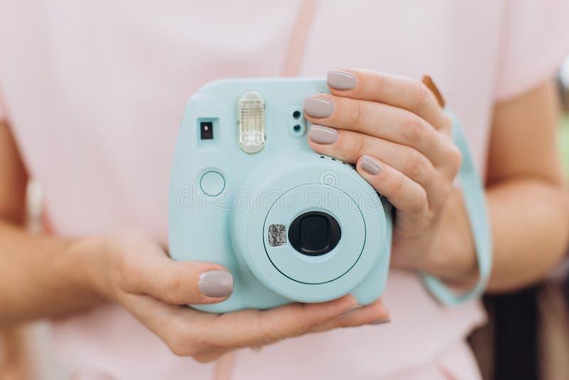 Manicure blu della ragazza delle mani della macchina fotografica istantanea della stampa fotografia stock