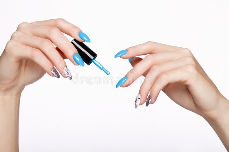Manicure blu di bella estate sulla mano femminile con smalto Primo piano immagine stock libera da diritti