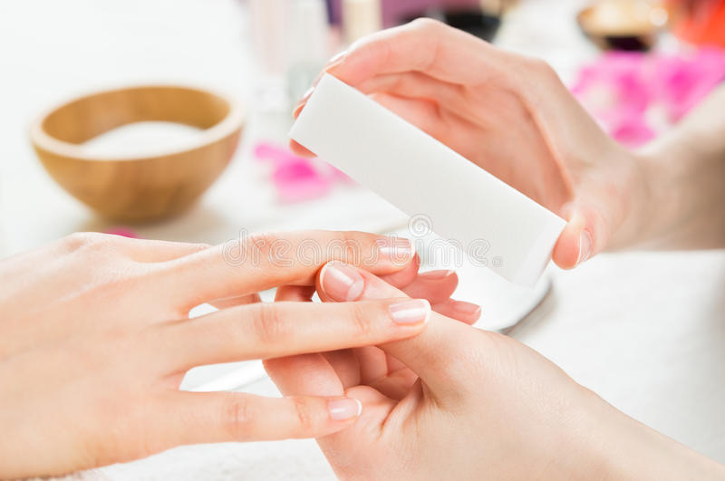 Manicure with buffer at nail salon stock image