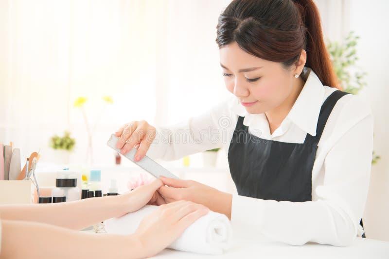 Manicure che fa lo sfregamento del chiodo mediante usando notropide immagini stock libere da diritti