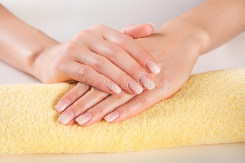 Manicure di Ombre della donna sulle mani delicatamente sull'asciugamano giallo fotografia stock