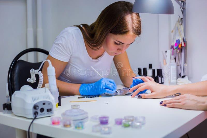 Manicure die cliënt behandelen bij schoonheidssalon die - op nai schilderen stock afbeeldingen