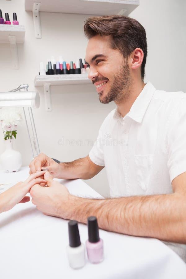Manicure die klant een manicure geven stock afbeeldingen