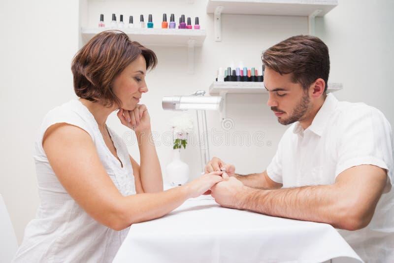 Manicure die klant een manicure geven royalty-vrije stock afbeelding