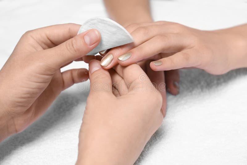 Manicure die poetsmiddel verwijderen uit de spijkers van de cliënt op witte stof royalty-vrije stock afbeeldingen
