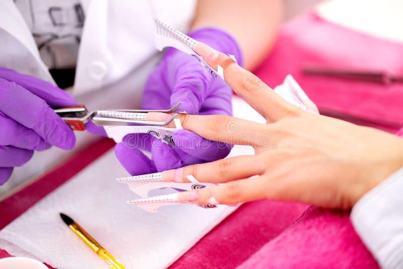Manicure die purpere handschoenen draagt die kunstmatige spijkerverhogingen plaatsen tijdens een manicurebehandeling royalty-vrije stock afbeeldingen