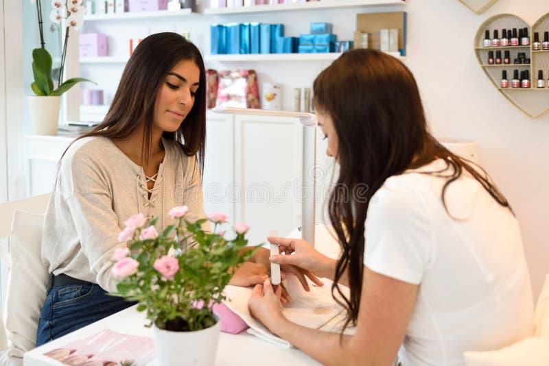 Manicure el cuidado del clavo para el cliente que se sienta en una tabla en el offi fotografía de archivo libre de regalías