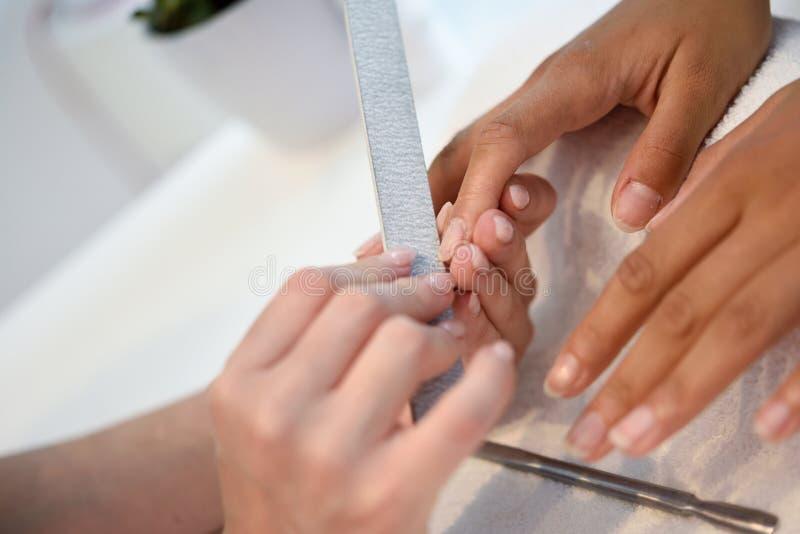Manicure el cuidado del clavo para el cliente que se sienta en una tabla en el offi fotografía de archivo