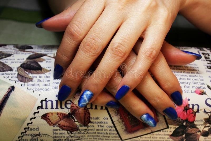 manicure eseguito dallo studente le mani si trova sopra su un cuscino di lavoro speciale sotto forma di barra Rivestimento blu co fotografia stock