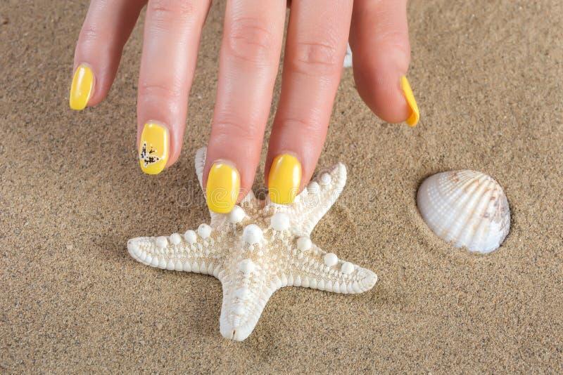 Manicure femminile con la lucidatura di unghie gialla a disposizione e stelle marine e coperture fotografie stock