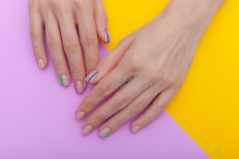 Manicure femminile d'avanguardia alla moda Le mani della bella giovane donna su fondo viola e giallo Vista superiore fotografia stock libera da diritti