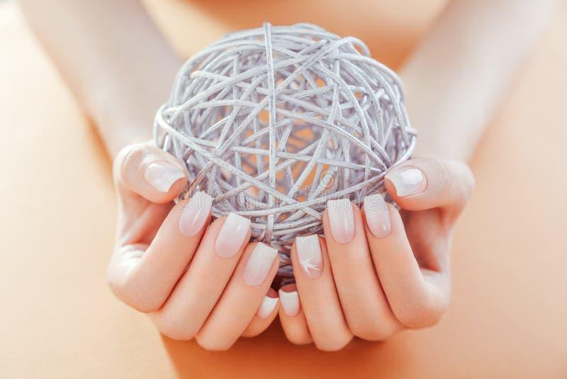 Manicure francese di Ombre su fondo arancio La donna con il manicure francese del ombre bianco e beige tiene una palla fotografia stock libera da diritti