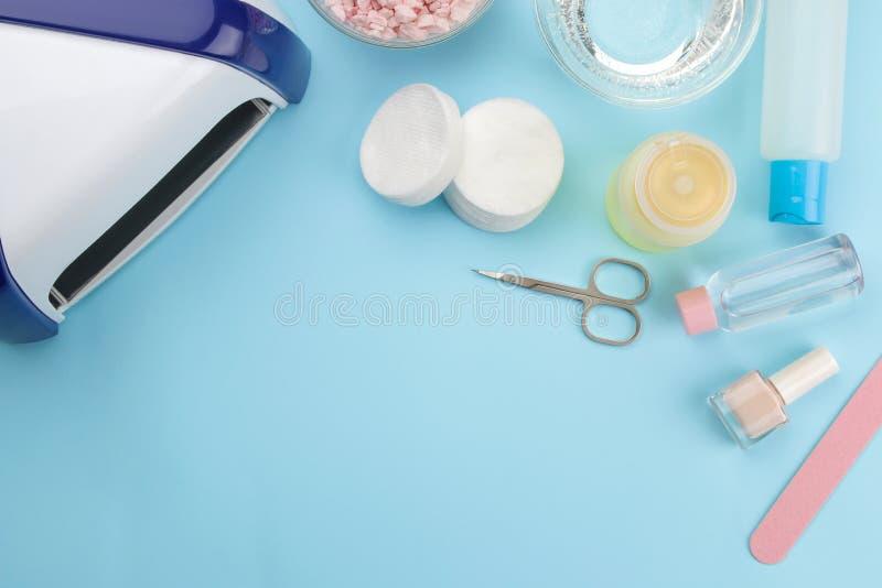 manicure gwoździ połysk, ULTRAFIOLETOWA lampa, różnorodni akcesoria i narzędzia dla manicure'u na modnym błękitnym tle, Odgórny w zdjęcia royalty free
