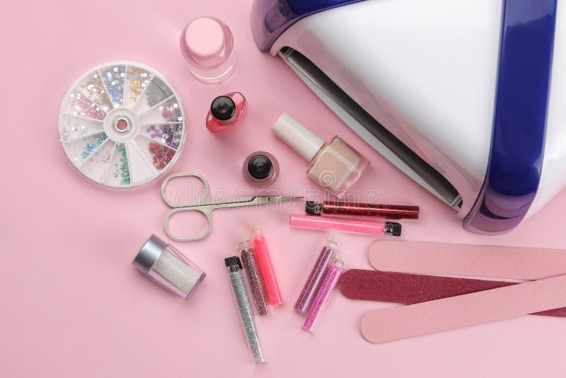 manicure gwoździ połysk, ULTRAFIOLETOWA lampa, różnorodni akcesoria i narzędzia dla manicure'u na modnym różowym tle, Odgórny wid fotografia stock