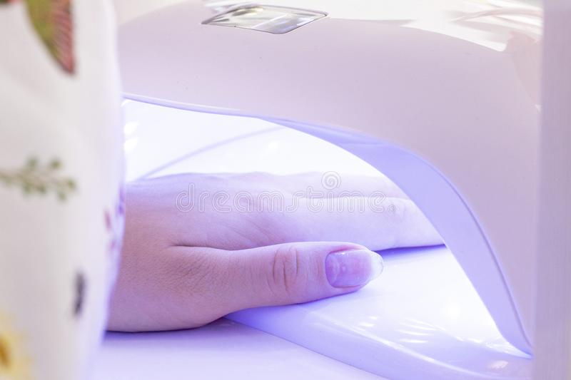 manicure hand i UV lampa att torka stelnar fernissa i lampan arkivbilder
