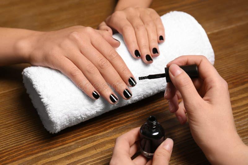 Manicure het schilderen de spijkers van de cliënt met poetsmiddel in salon stock afbeeldingen
