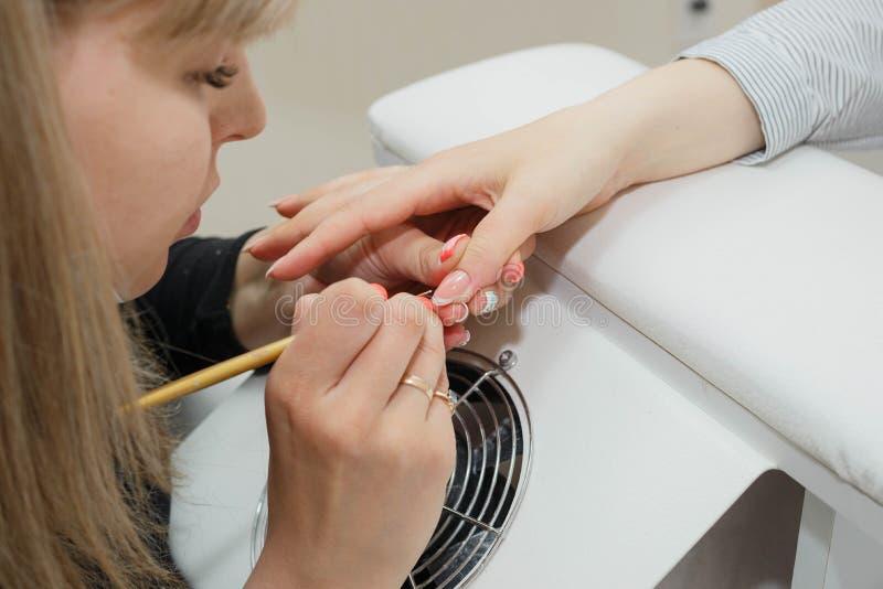 manicure Il supervisore fa l'estensione del chiodo: illustrazione del gel bianco sul bordo libero di un chiodo fotografia stock