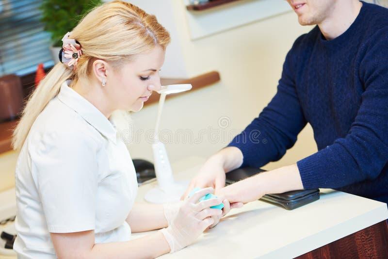 Manicure a la mujer del especialista que hace cuidado del clavo del finger del correo fotos de archivo libres de regalías