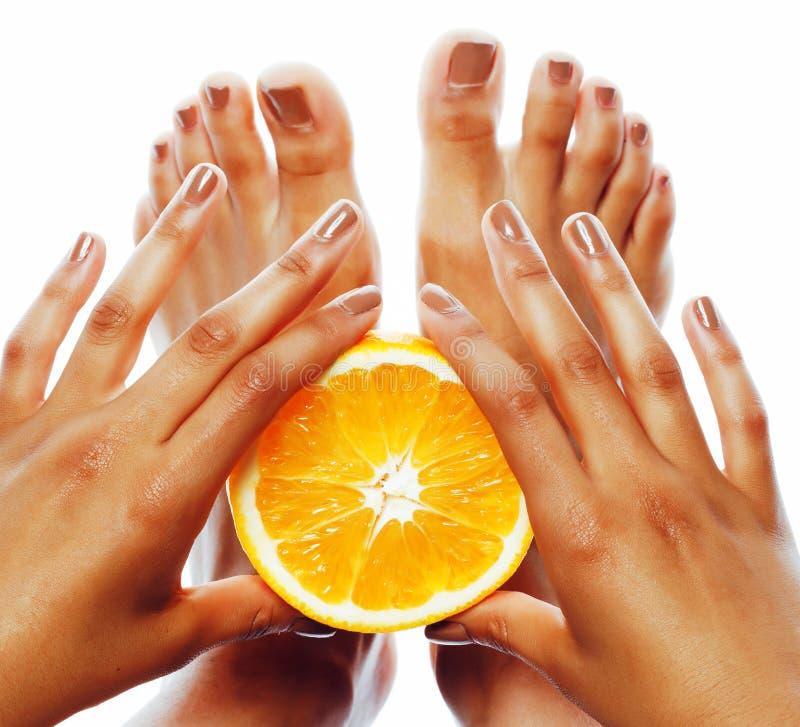 Manicure la pedicura en las manos afroamericanas de la piel del tann que sostienen la naranja, concepto de la atención sanitaria imagen de archivo
