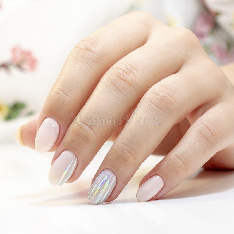 manicure manicurzysta robić manicure i gel na klientów gwoździach w delikatnych brzmieniach z lampasami foliowa glosa polerować zdjęcia stock