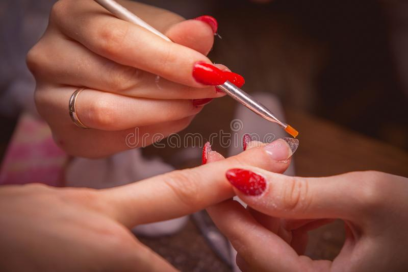 Manicure. Master make nail extension stock images