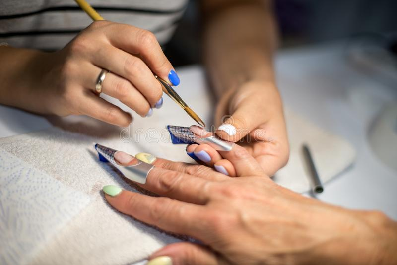 Manicure. Master make nail extension. hands closeup. royalty free stock photography