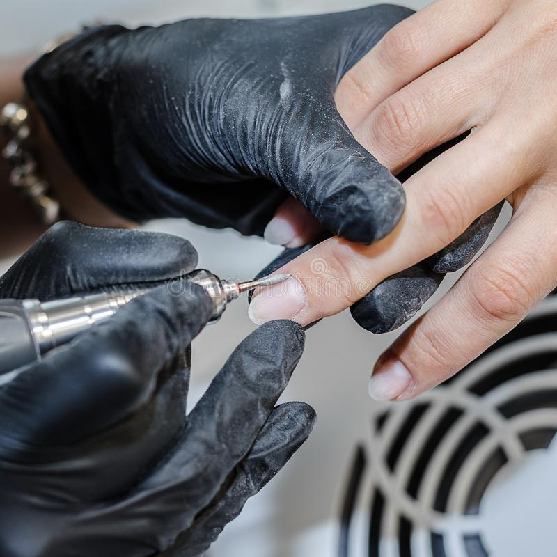 The manicure master makes a hardware manicure with a milling cutter. stock image