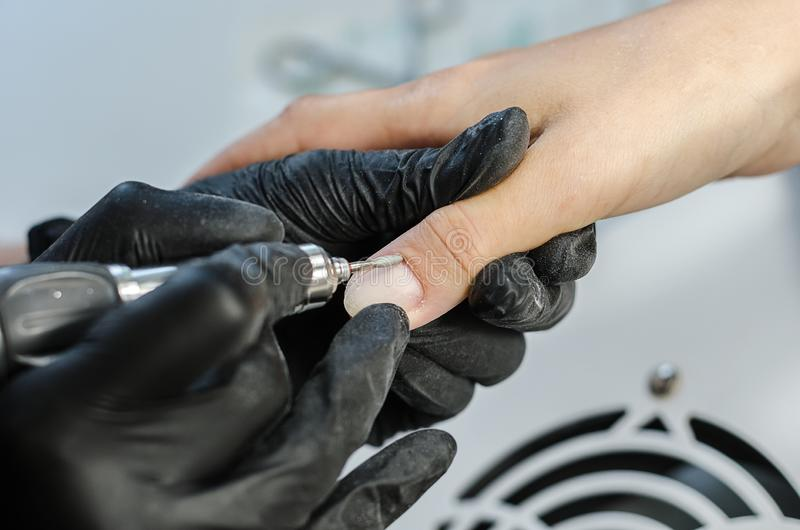 The manicure master makes a hardware manicure with a milling cutter. stock photography