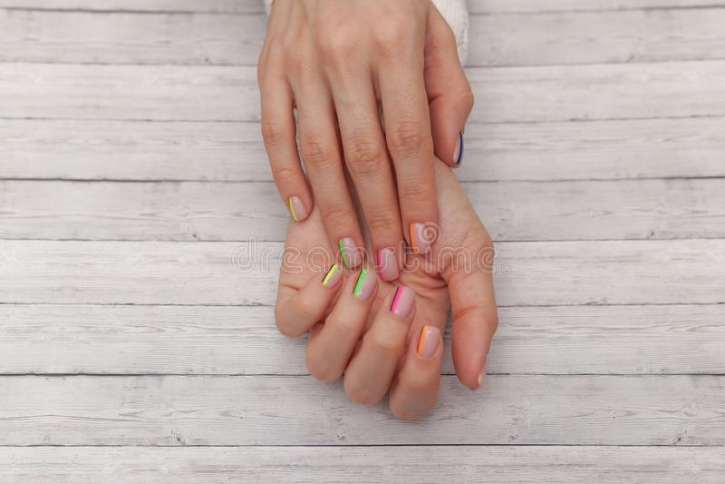 Manicure moderno multicolore, progettazione dell'unghia Umore di estate, su fondo di legno Vista superiore fotografia stock libera da diritti