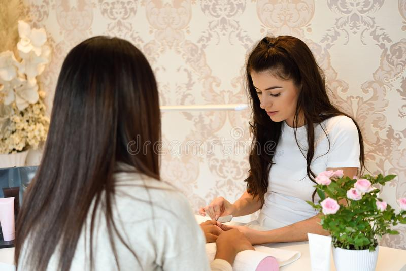 Manicure nail care for the client sitting at a table in the office. royalty free stock images