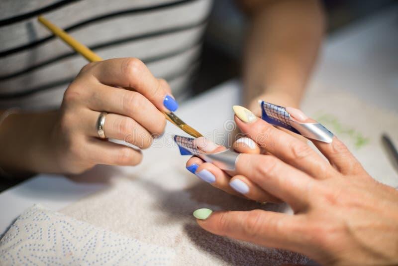 manicure O mestre faz a extensão do prego entrega o close up fotos de stock royalty free