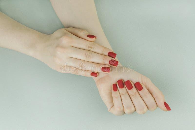 Manicure opaco rosso alla moda, forma quadrata fotografia stock libera da diritti