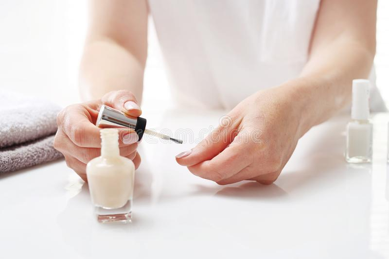 Manicure. Painting of nails. The woman is painting her nails stock photography