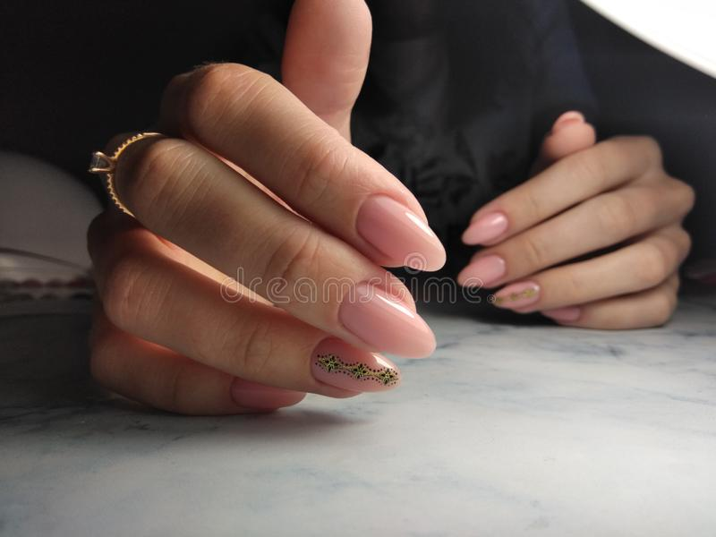 Manicure with peach camouflage gel lacquer with design stock photo