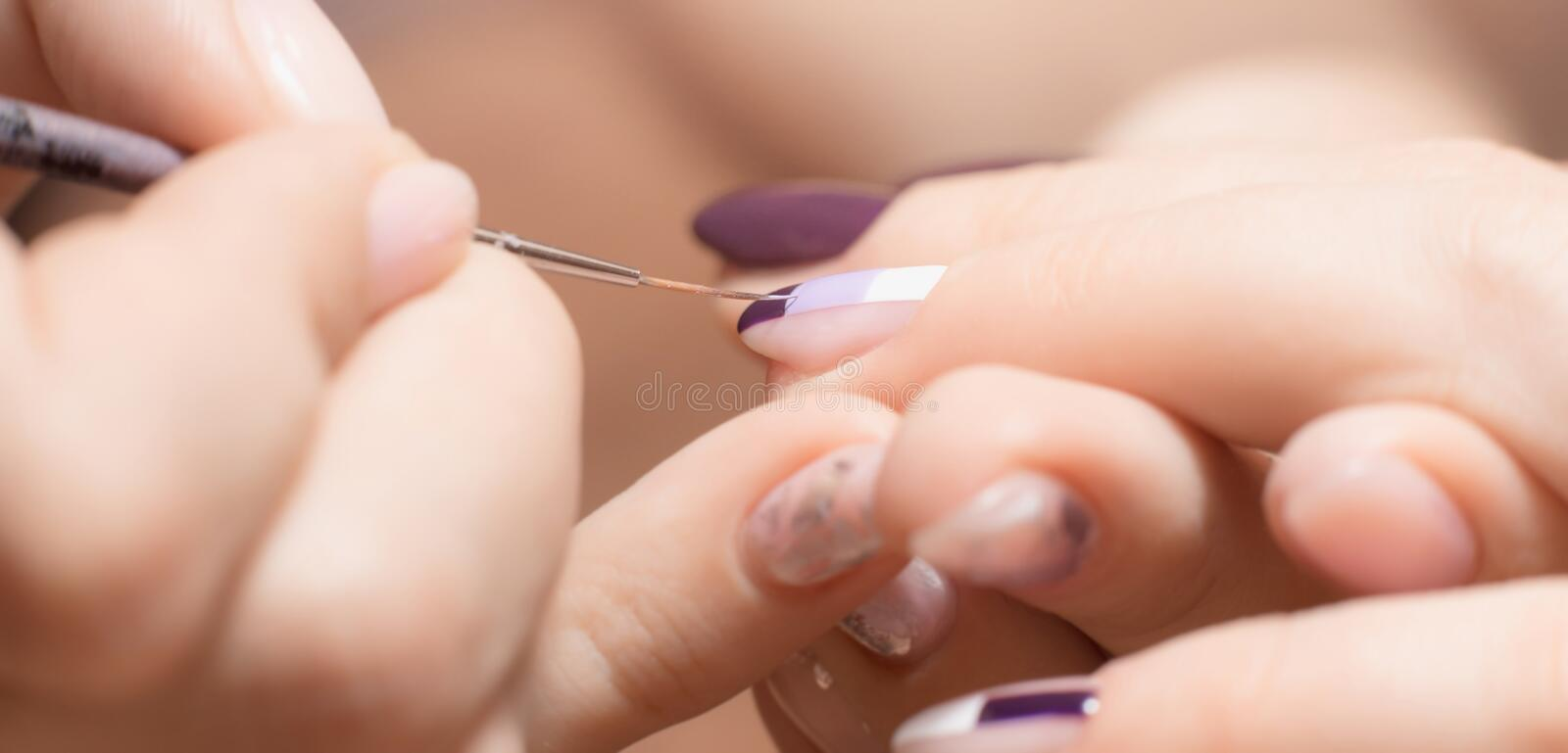Manicure and pedicure. Closeup of banner drawing picture on nail in manicure salon. Hand care concept stock images