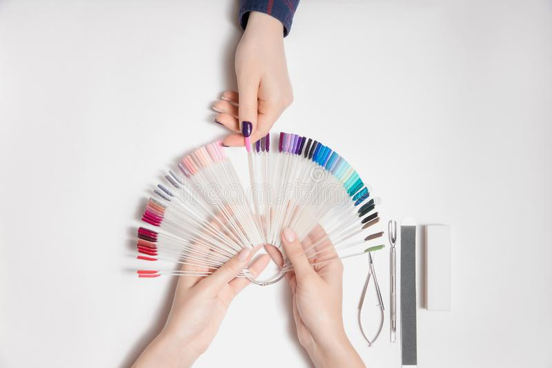 Manicure and pedicure. Master woman manicurist chooses color of nail polish from palette with her finger. White isolated background. Top view stock images