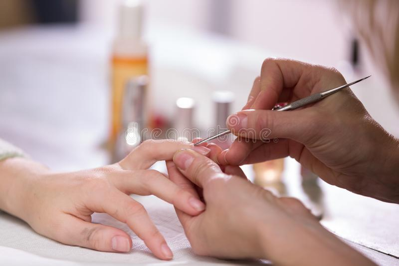 Manicure process. Woman works on younger girl`s hands and nails. Close-up. stock photo