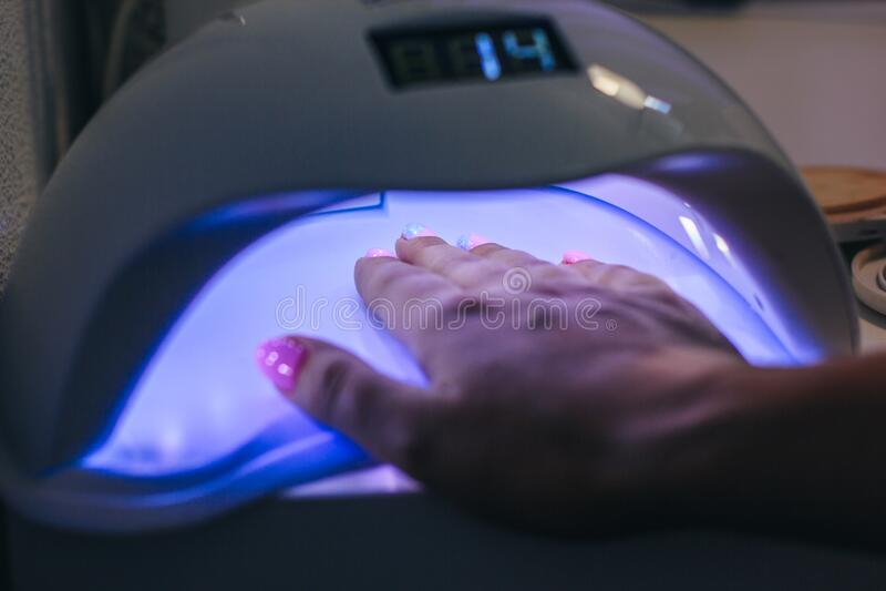 Manicure professionali in salone Lampada a raggi UV in bianco Chiudi concetto Sfondo di bellezza Chiodi di manicure lucidati a ma fotografie stock libere da diritti